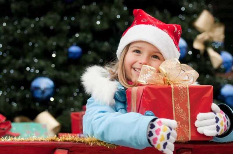 Child with present in hands in front of Christmas tree