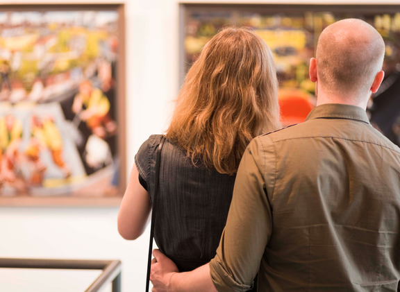 couple walking round a gallery or museum looking at paintings